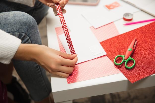 Chiuda sulle mani femminili che fanno la cartolina d'auguri per il nuovo anno e il natale