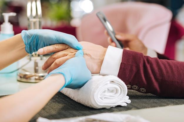 Chiuda in su delle mani femminili che massaggiano le mani maschili e indossano guanti blu