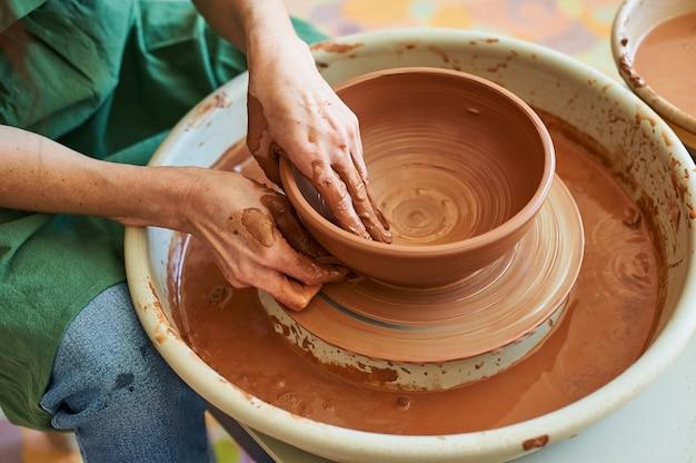 Primo piano delle mani femminili di un maestro vasaio che lavora su una ruota con argilla