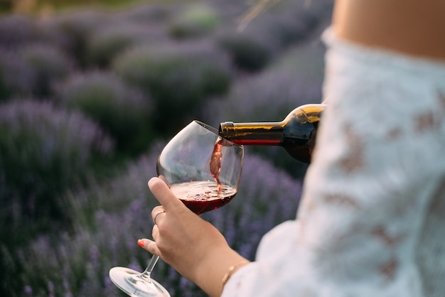 Primo piano di mani femminili versando il vino rosso in un grande bicchiere nel campo di lavanda