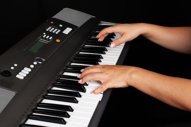 Primo piano delle mani femminili premendo i tasti su un sintetizzatore elettronico o un pianoforte
