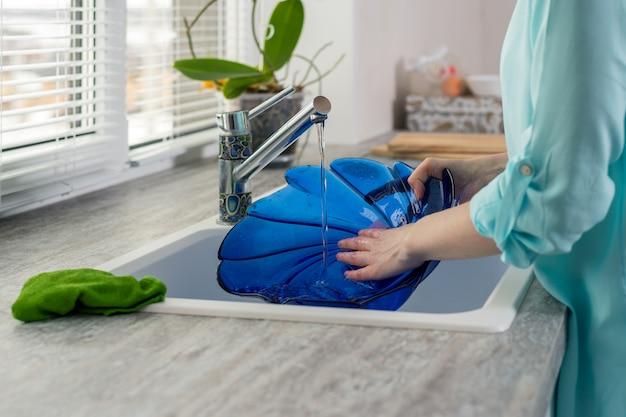 Il primo piano delle mani femminili risciacqua il piatto blu sotto la pressione dell'acqua nel lavandino della cucina davanti alla finestra