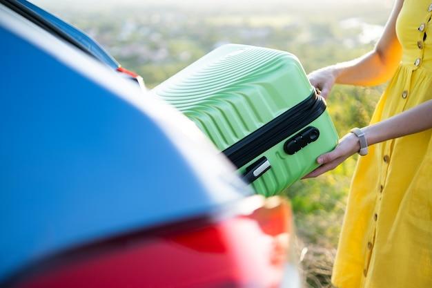 Chiuda in su delle mani femminili che prendono la valigia verde dal bagagliaio dell'auto. concetto di viaggi e vacanze.