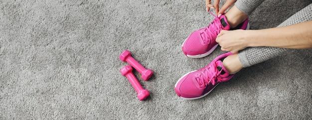 Primo piano delle mani femminili che legano i lacci delle calzature di addestramento prima dell'allenamento al coperto, manubri nelle vicinanze