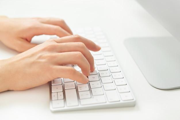 Primo piano di mani femminili digitando sulla tastiera del computer, imprenditrice lavorando in ufficio e utilizzando il computer.