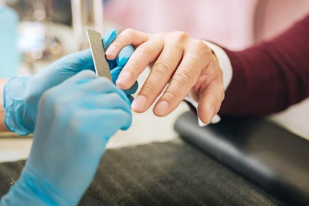 Primo piano di mani femminili che indossano guanti e l'applicazione di file