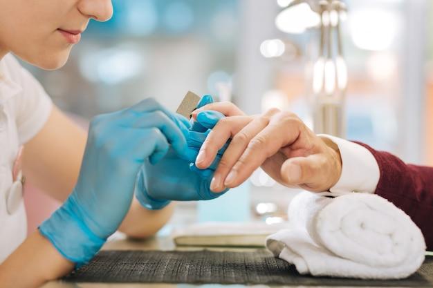 Primo piano di mani femminili che indossano guanti e utilizzando il file