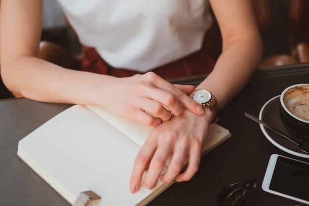 Primo piano di mani femminili con orologio elegante