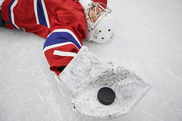 Primo piano di giocatore di hockey femminile sdraiato sul ghiaccio e tenendo spennare esaurito dopo l'allenamento