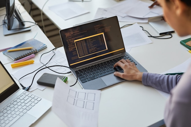Primo piano di una donna sviluppatrice it che scrive codice durante l'utilizzo del laptop in ufficio con un team di ingegneri software, spazio di copia