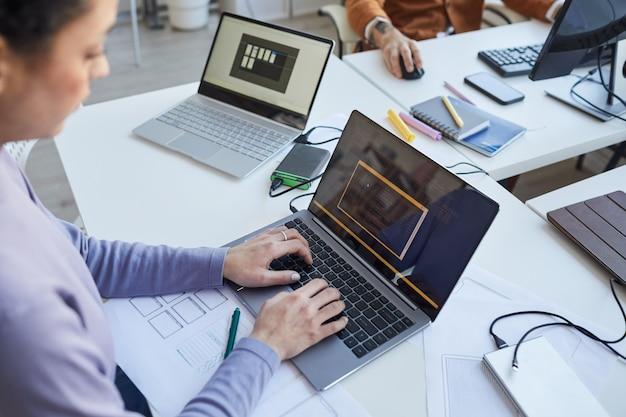 Primo piano di una programmatrice it femminile che scrive codice sullo schermo del laptop mentre collabora al progetto con un team di sviluppatori software, copia spazio