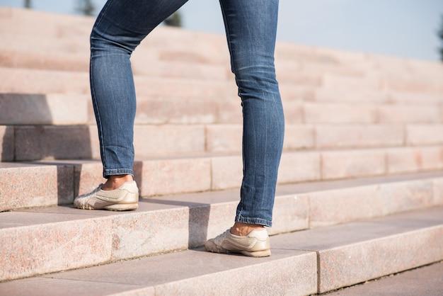 Primo piano di gambe femminili che salgono i gradini.