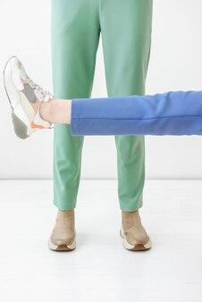 Primo piano delle gambe femminili che mostrano vestiti e scarpe sulla scena bianca all'interno