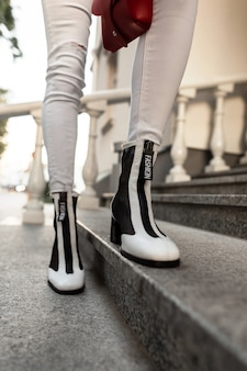 Primo piano delle gambe femminili in jeans alla moda in scarpe alla moda per strada.