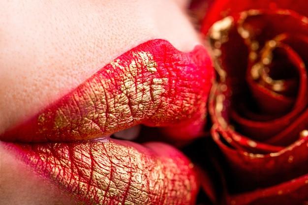 Primo piano delle labbra femminili con rosa rossa. labbra femminili sexy del primo piano con rossetto di colore rosso. labbra delle donne e fiore rosso. labbra sensuali. donna con fiore di rosa. orli femminili sexy del primo piano con rossetto rosso.