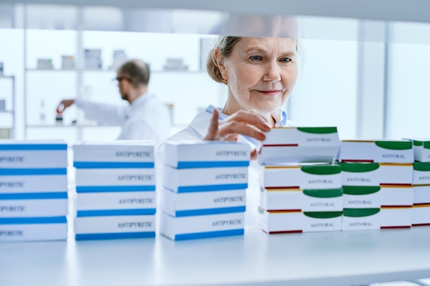 Avvicinamento. farmacista femminile in piedi davanti a uno scaffale di medicinali. foto con copia-spazio.