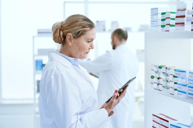 Avvicinamento. farmacista femminile con una tavoletta digitale in piedi vicino a uno scaffale con farmaci.