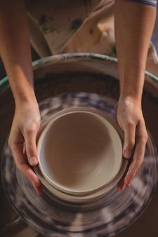 Primo piano del vasaio femminile che fa vaso
