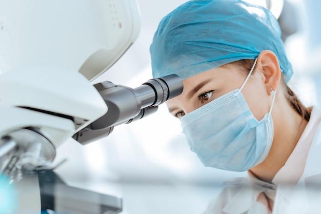 Avvicinamento. scienziato femminile utilizzando un microscopio in un laboratorio medico. scienza e tutela della salute.