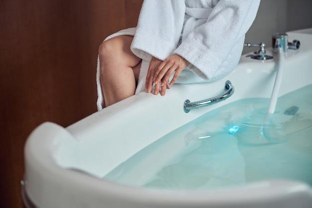 Primo piano su una donna in accappatoio di spugna seduta sul bordo della vasca