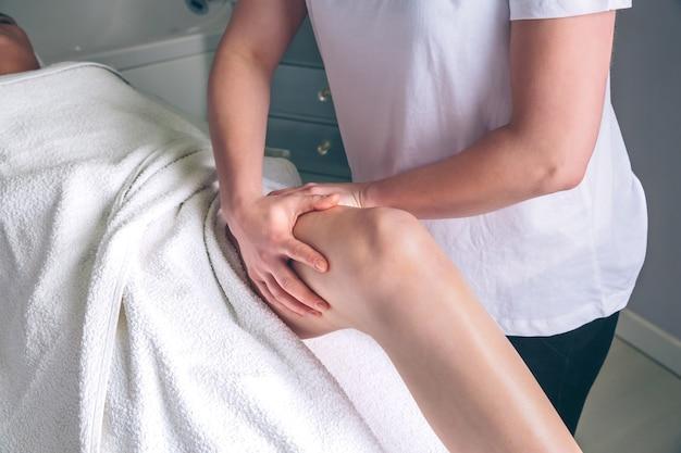 Primo piano delle mani del terapista femminile che fanno massaggio linfodrenante sulle gambe della donna in un centro clinico. medicina, sanità e concetto di bellezza.