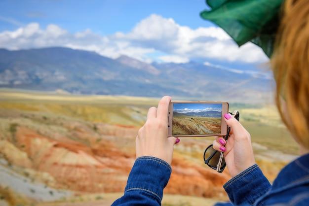 Primo piano del turista femminile spara incredibile fenomeno naturale sul suo smartphone.