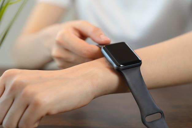 Primo piano della femmina che indossa in applicazione orologio intelligente.