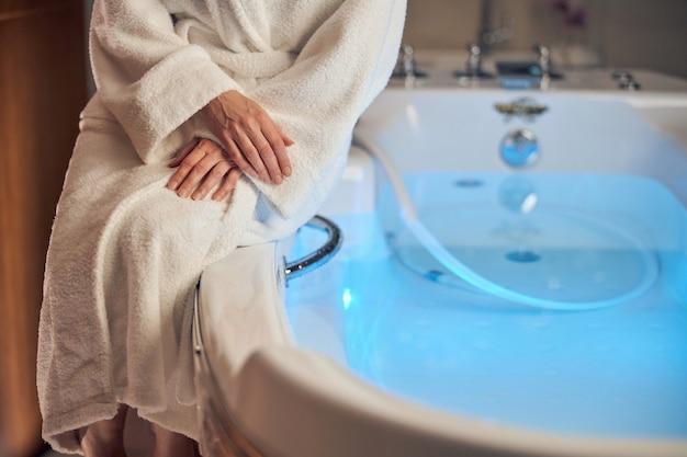 Primo piano su una donna con le mani incrociate seduta sul bordo della vasca da bagno