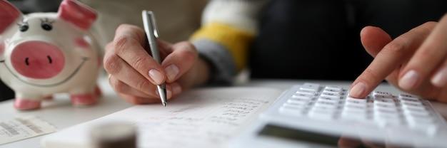 Primo piano del bilancio familiare femminile di scrittura e di contabilità. salvadanaio per risparmiare.
