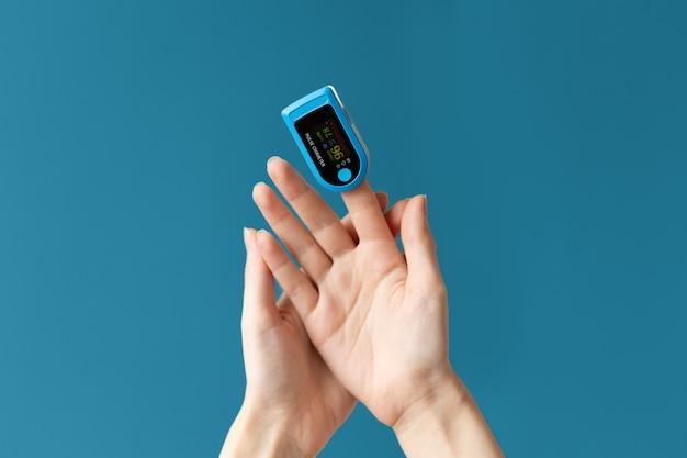 Primo piano della mano delle femmine con un pulsossimetro posizionato sul dito indice. sfondo blu. il concetto di misurazione dell'ossigeno nel sangue.