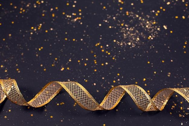 Chiuda in su del nastro metallico di bronzo dorato festivo su sfondo nero glitter