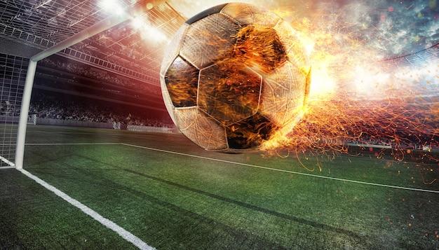 Primo piano di un pallone da calcio infuocato preso a calci con potenza allo stadio segnando un goal