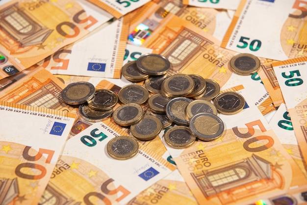 Primo piano di cinquanta banconote e monete in euro. denaro contante.