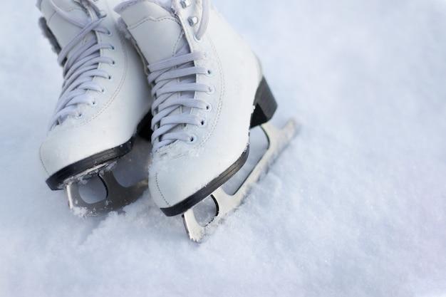 Primo piano dei pattini di figura su un ghiaccio. pattinaggio sul ghiaccio attività all'aperto con la famiglia in inverno.