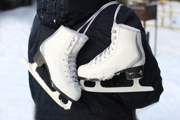 Primo piano dei pattini di figura sulla spalla di un adolescente. pattinaggio sul ghiaccio all'aperto con la tua famiglia in inverno.