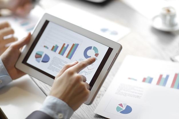 Primo piano. relazione finanziaria sullo schermo della tavoletta digitale. persone e tecnologia