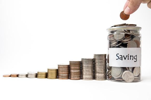 Chiuda sulla moneta dei soldi di goccia della mano e del dito al vaso con le monete della crescita che impilano con la parte posteriore di bianco