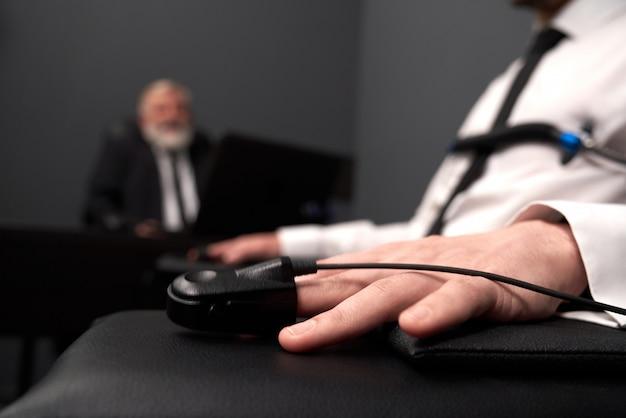 Chiuda in su del sensore della barretta del poligraph sul dito maschio.