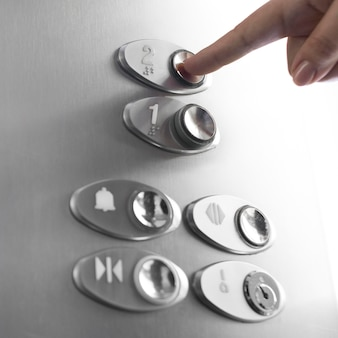 Primo piano dito toccando il pulsante dell'ascensore