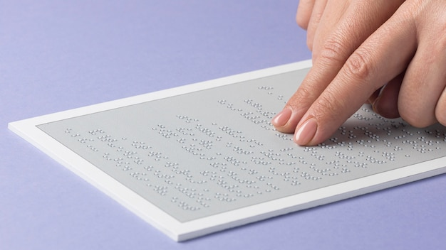 Dita del primo piano che leggono documento braille