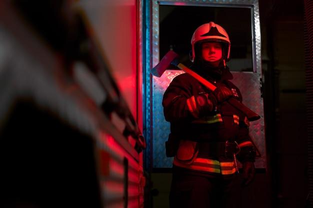 Primo piano vigile del fuoco con martello sulla spalla in piedi vicino all'autopompa dei pompieri