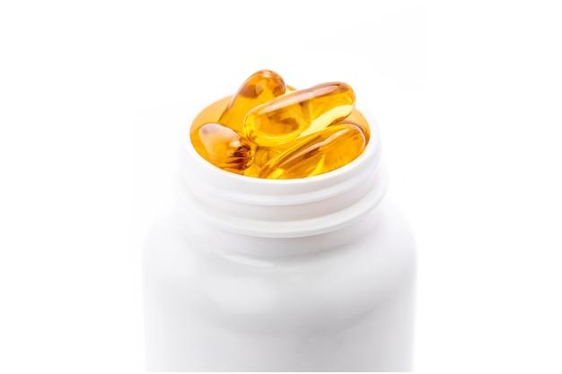 Primo piano di capsule di supplemento di olio di pesce per la salute all'interno di una bottiglia di plastica bianca isolata su sfondo bianco