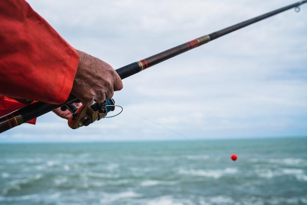 Primo piano di un pescatore che tiene una canna da pesca. concetto di pesca e sport.