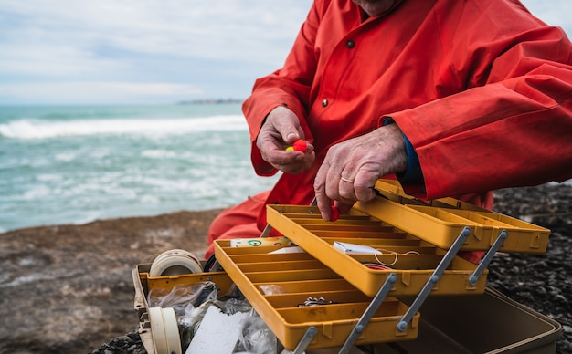 Primo piano di un pescatore che mette sull'esca con la scatola dell'attrezzatura di pesca.