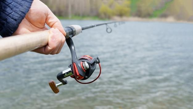 Primo piano di una canna da pesca in mano sopra il fiume, pescando