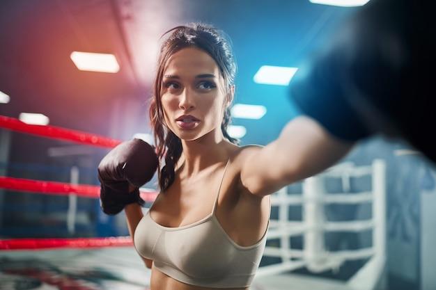 Chiuda in su dei guanti di inscatolamento da portare concentrati adatti della donna del brunette