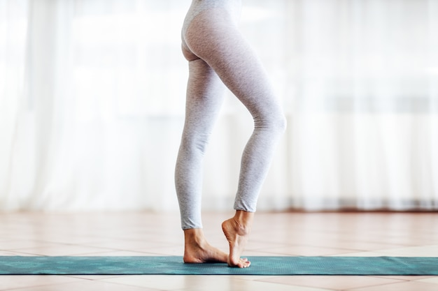 Close up fit slim yogi ragazza in piedi sulla stuoia a piedi nudi.
