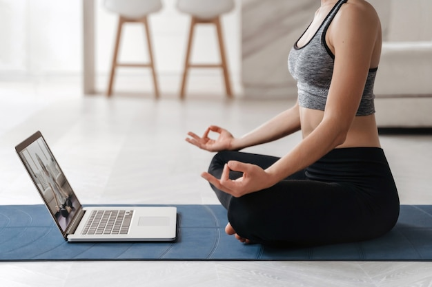 L'allenatore della donna in forma da vicino ha una formazione online video su internet di hatha yoga, praticando la postura sukhasana
