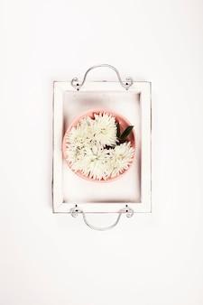 Chiuda in su dei fiori che galleggiano in ciotola di acqua