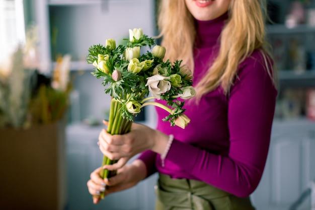 Close-up fiori in mano. fiorista sul posto di lavoro. donna che organizza un bouquet di rose, crisantemi, garofani e altri fiori. un insegnante di fiorai in masterclass o corsi.